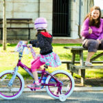 Woman giving thumbs up to girl on a bike